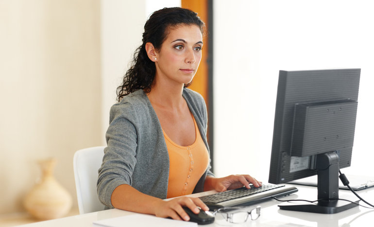 Young woman sitting in front of a computer with her hand on the mouse